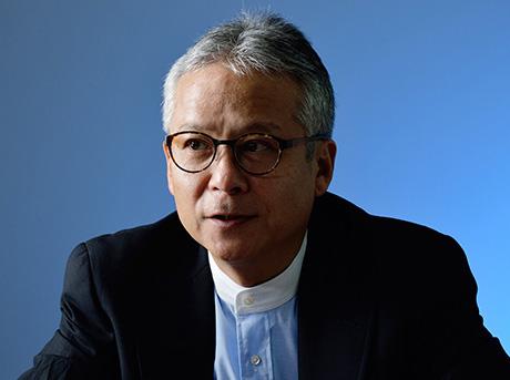 Il professore Iroshi Ishii con occhiali e giacca su sfondo celeste neutro