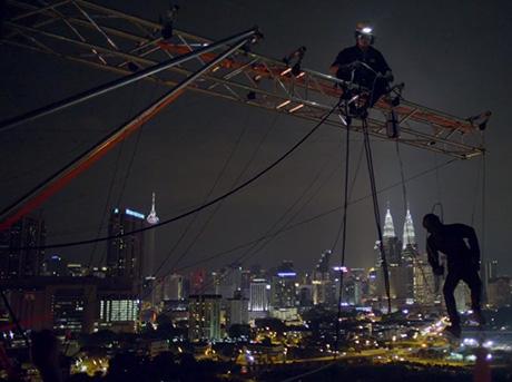 Operaio con casco notturno su di una gru mentre sposta un manichino sorretto da cavi metallici
