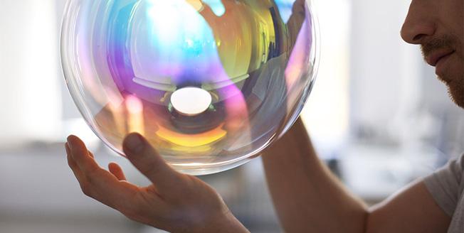 Un uomo regge una sfera di vetro con riflessi arcobaleno sulla superficie