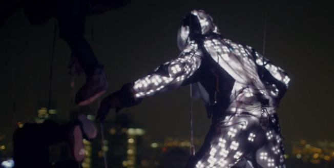Fotogramma di un video uomo appeso con cavi indossa una tuta ricoperta di sensori elettrici