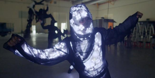 Fotogramma di un video uomo con tuta ricoperta di sensori appeso al soffitto con cavi