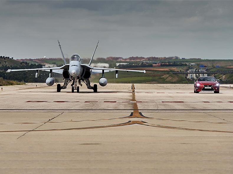 LC 500 rossa e jet ai blocchi di partenza su pista di aeroporto