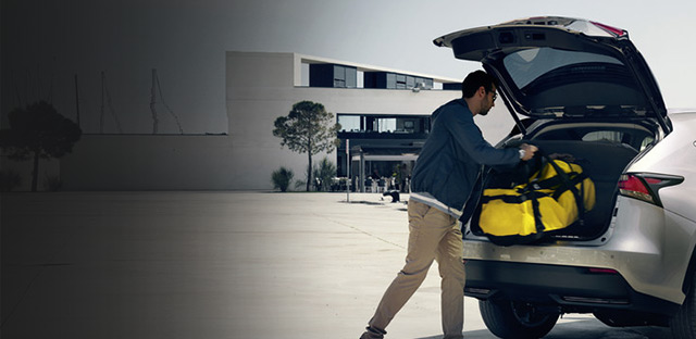 Il proprietario di un NX Hybrid Icon mentre carica i propri bagagli in maniera pratica e semplice grazie al portellone posteriore ad azionamento automatico della vettura