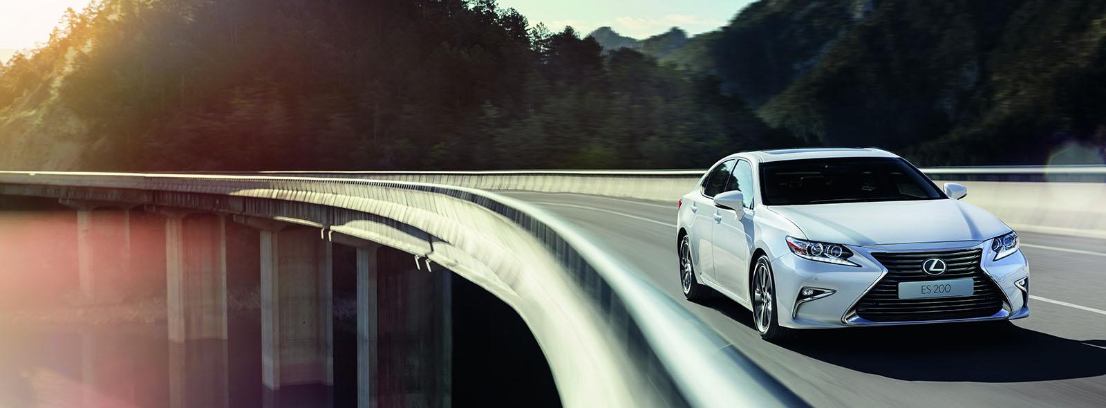Mirvari ağ Lexus ES 200 avtomobili körpü üzərində hərəkətdə