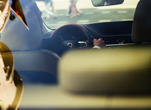 Bej interyerli Yeni Lexus ES 200 avtomobilinin sükanı arxasında kişi