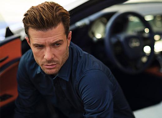 Мужчина сидящий в Lexus LC с открытой дверью