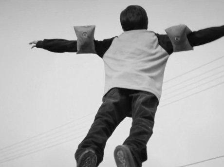 Vista trasera de niño volando con manguitos
