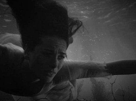 Mujer buceando en lago con cara de preocupación