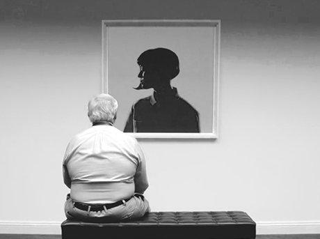 Hombre mayor sentado de espaldas en banco observando cuadro
