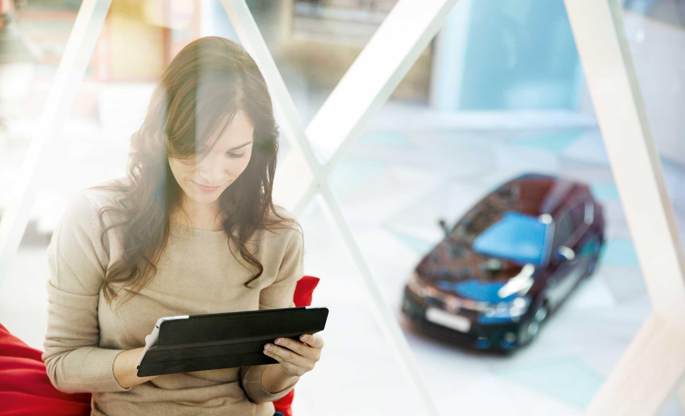 Mujer consultando tableta con Lexus aparcado en el exterior