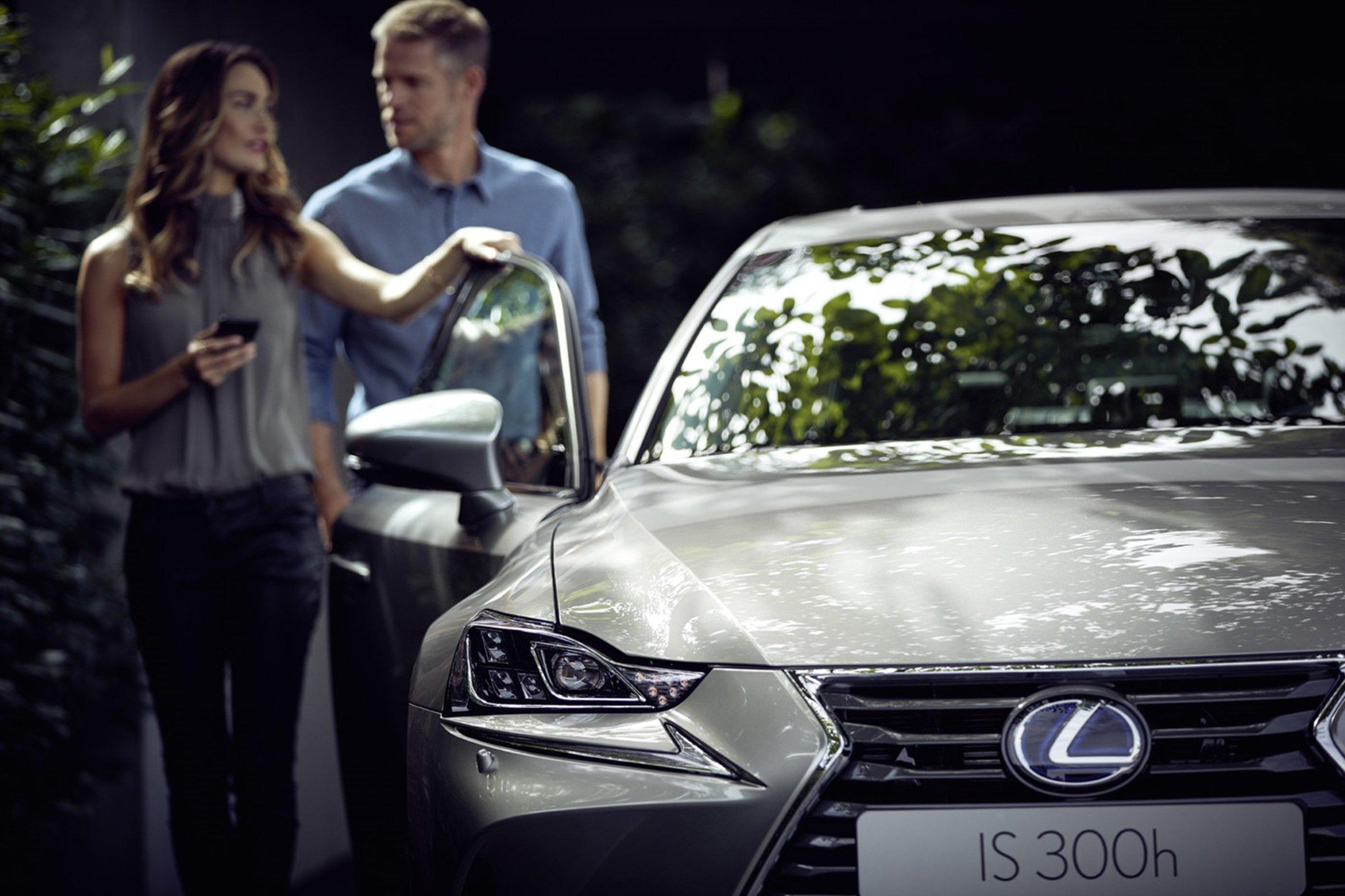 Vista frontal de una pareja de propietarios del nuevo Lexus IS 300h gris junto al vehículo