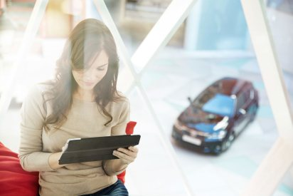 Mujer consultando tableta y con coche de fondo
