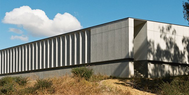 Edificio con espejos destacan en medio de los matorrales aportando un toque futurista