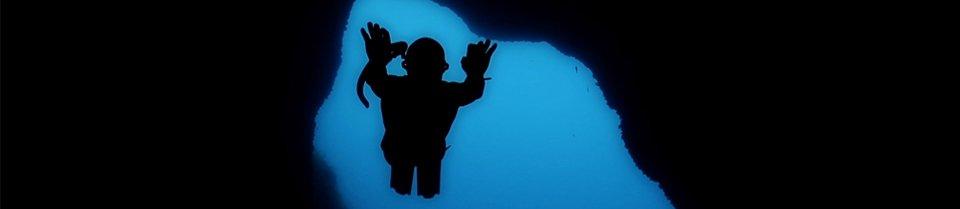 Escena de buceador entrando en cueva submarina