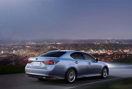 GS Hybrid 300h color argento su strada in collina con sfondo di luci di città