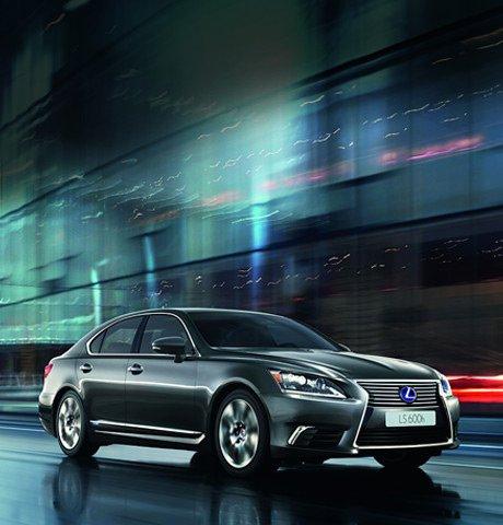 LS Hybrid nera su strada di sera e sullo sfondo un palazzo moderno a vetri
