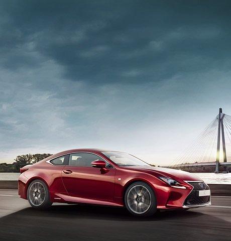 Vista laterale della coupè RC Hybrid F Sport colore rosso con sfondo cielo sereno