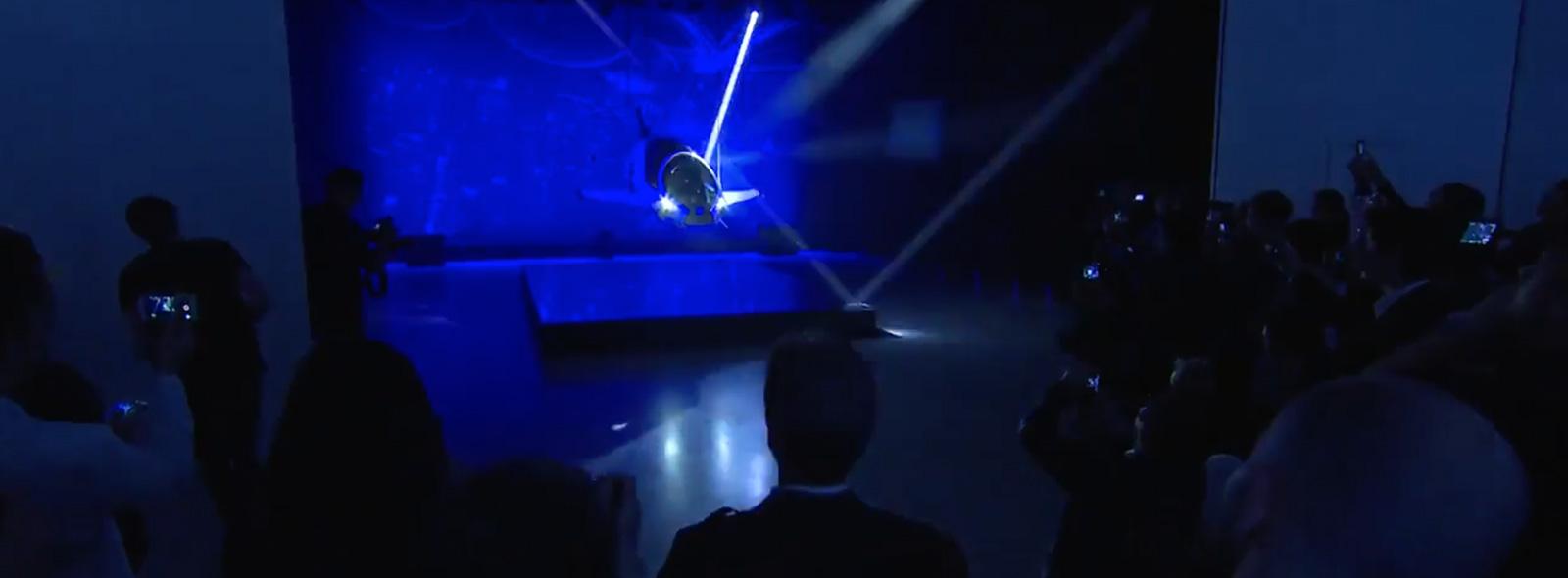 I fari frontali dello SkyJet illuminano una sala scura allestita per il lancio del film Valerian