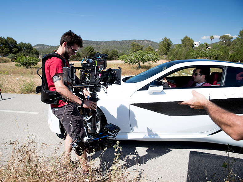 Un operatore davanti alla nuova LC bianca filma Mark Ronson che siede al posto di guida