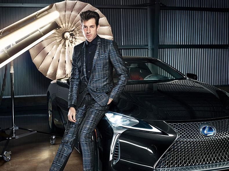 Mark Ronson con un abito elegante nero seduto sul cofano della nuova LC colore nero brillante