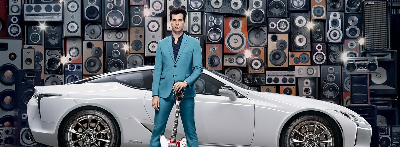Mark Ronson in abito blu in posa con una chitarra e la nuova LC bianco perla davanti una parete di casse stereo