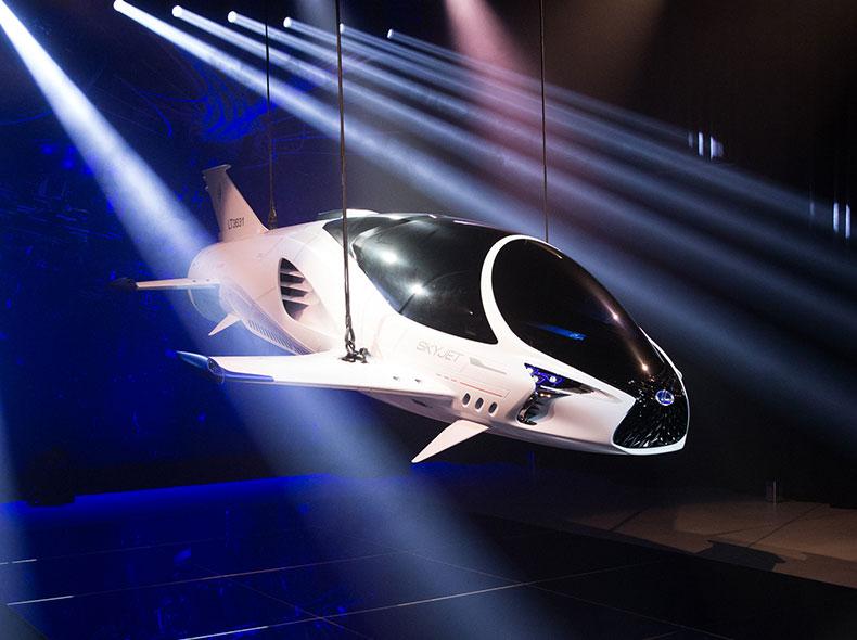 Vista frontale diagonale del Lexus SkyJet sorretto da alcuni cavi in uno spazio espositivo
