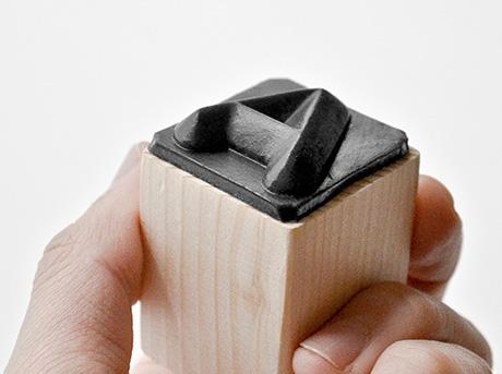 Un carattere tipografico occidentale in rilievo su un parallelepipedo di legno del progetto INSTAMP