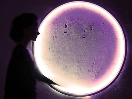 La designer Marina Mellado Mendieta passa davanti ad una sfera di luce
