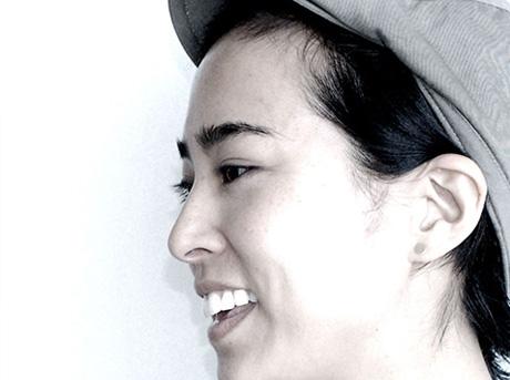 Profilo del designer Nao Tamura mentre sorride indossando un cappello
