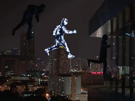 Sagoma di tre manichini in posa da salto di cui uno illuminato con sfondo città