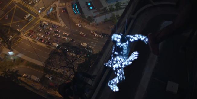 Fotogramma di un video un uomo con tuta ricoperta di sensori elettrici si arrampica su un palazzo