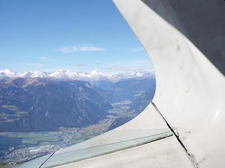 Dettaglio ala di un aereo e sullo sfondo paesaggio di montagna con neve