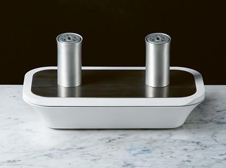 Oggetto di design con una base in legno e bianco con due cilindri in argento