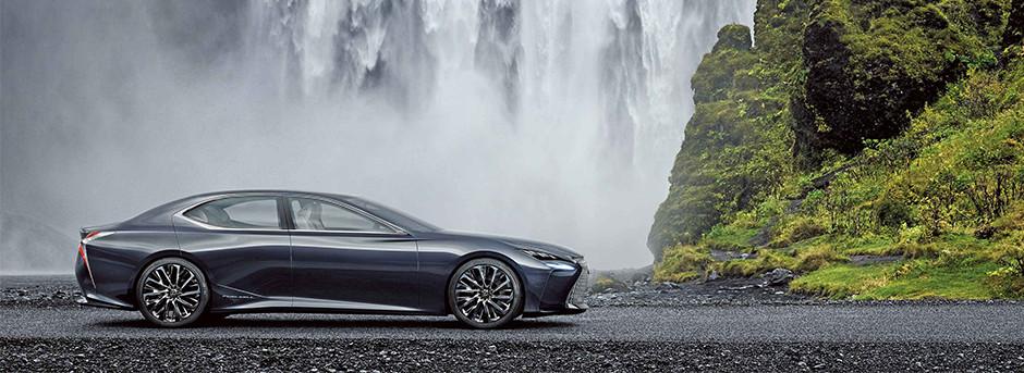 Vista laterale di una Lexus colore grigio scuro davanti ad una cascata