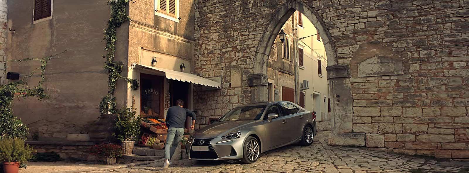Nuova IS Hybrid argento in sosta davanti un fruttivendolo in un centro storico di un paese italiano