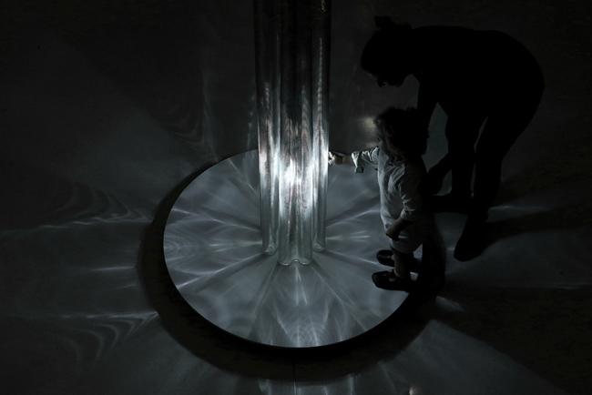 Una donna e una bambina interagiscono con un'installazione di design