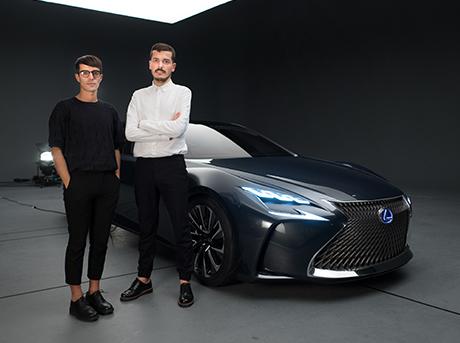 Due designer in primo piano in piedi davanti alla concept car LF FC colore grigio scuro