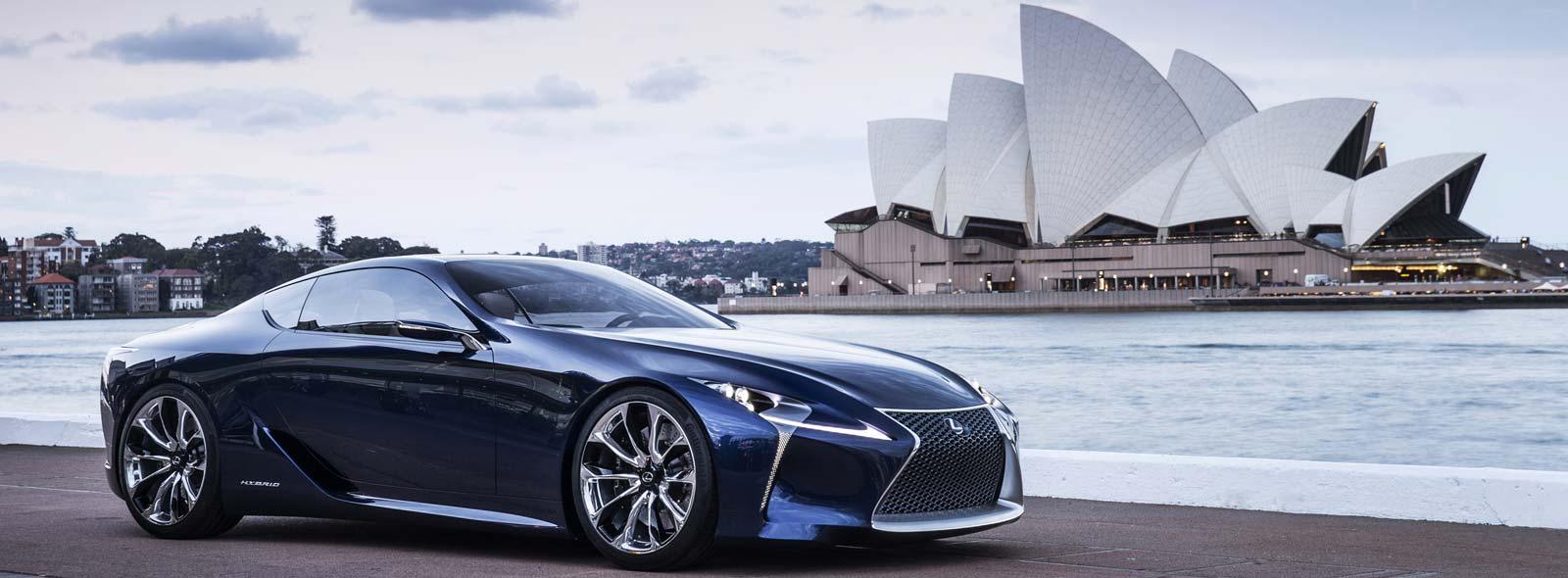 Vista laterale del coupé LF LC colore blu e sullo sfondo il Sidney Opera