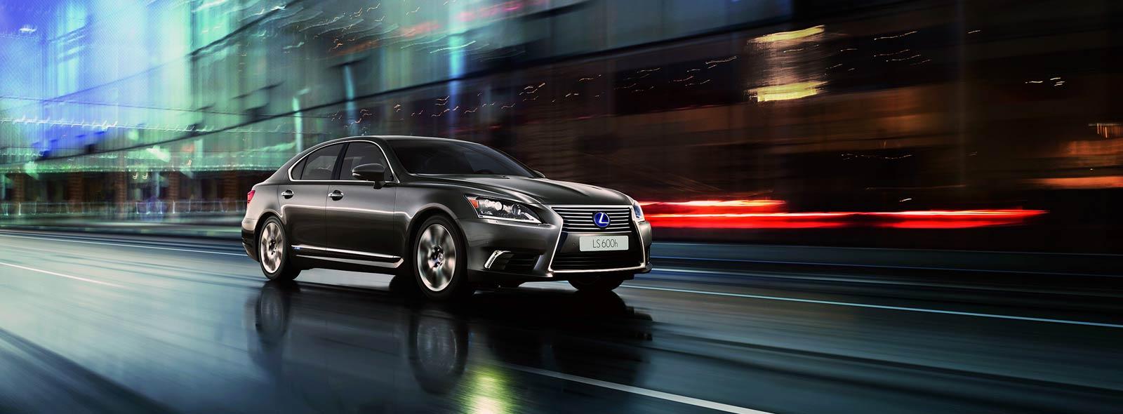 Lexus LS Hybrid colore argento su strada di città e sullo sfondo un edificio in vetro