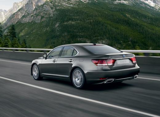Lexus LS Hybrid colore grigio scuro mentre percorre un ponte su strada di montagna