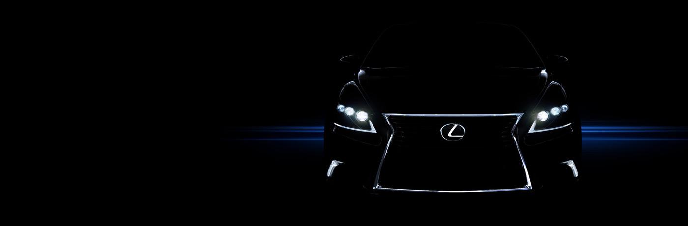 Vista frontale auto con dettagli luci fari e logo Lexus su griglia a clessidra