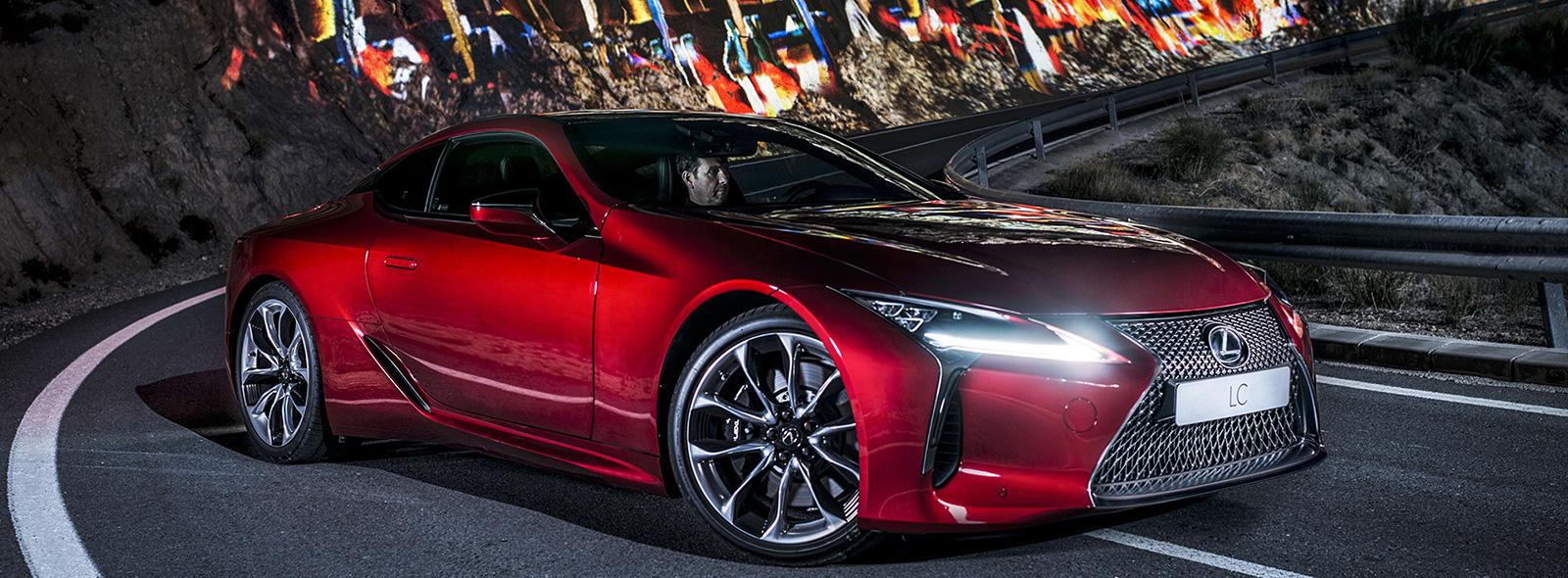 Vista frontale della nuova LC rosso brillante in curva di notte su strada montana