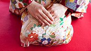 Donna giapponese con kimono piegata sulle ginocchia e mani conserte sulle gambe