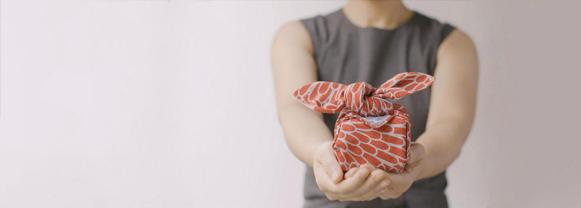 Donna che porge un pacco infiocchettato in dono