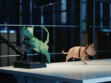 Due origami di un gatto verde e marrone saltano su di una scrivania da ufficio