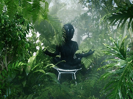 Una donna con tuta nera aderente in pelle e casco integrale seduta tra piante equatoriali