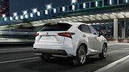 NX Hybrid F SPORT bianco che percorre una strada urbana di sera