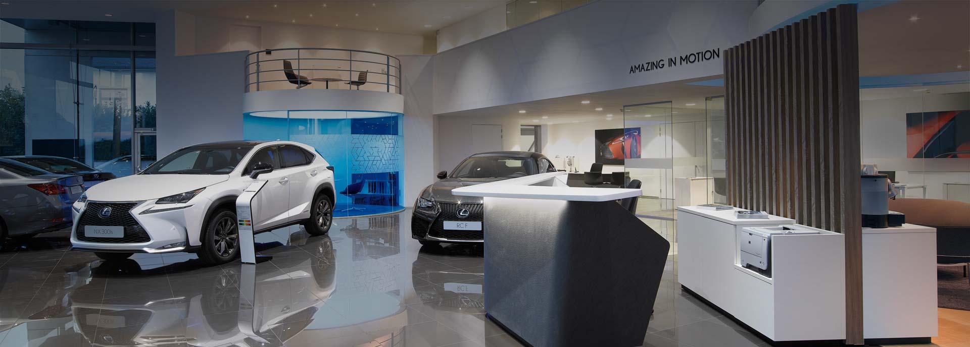 Interno di un concessionario Lexus con una NX 300h e una RCF in mostra