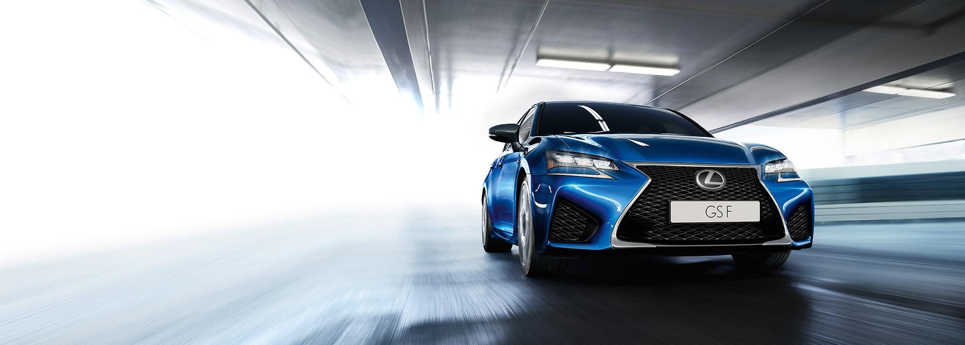 Vista frontale della nuova berlina sportiva GS F colore blu transita sotto un cavalcavia urbano