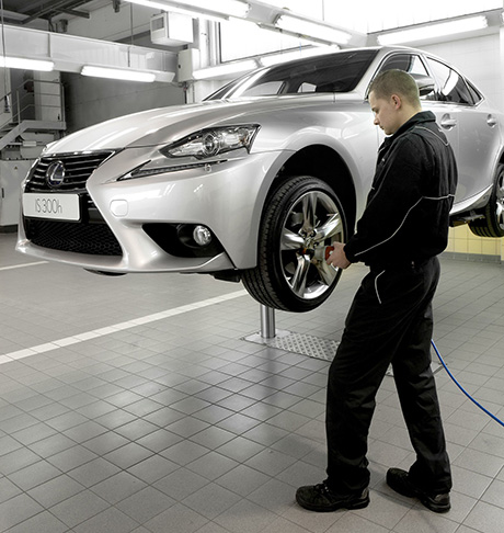 Un meccanico Lexus avvita i bulloni di una Lexus Hybrid